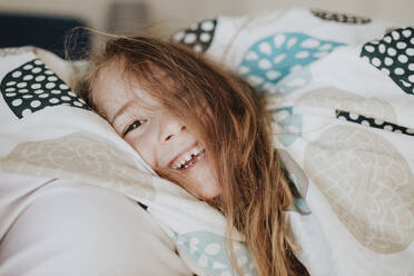 Smiling girl wrapped in blanket on bed at home - GMLF01015