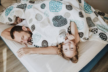 Smiling girl with father and brother lying on bed under blanket at home - GMLF01018
