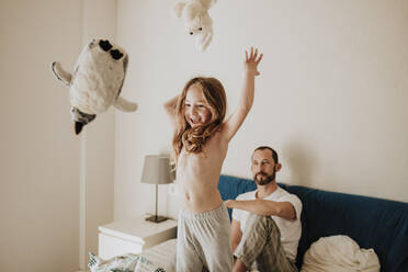 Cheerful girl throwing stuffed toys while father watching on bed at home - GMLF01021