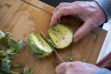 Senior man cutting artichoke on cutting board - AFVF08239