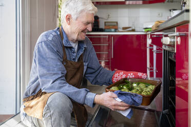 Smiling senior man putting vegetable tray in oven - AFVF08242