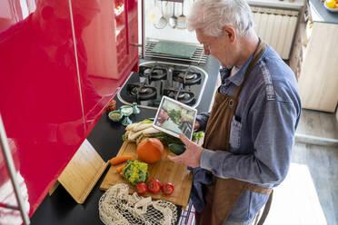 Senior man cooking at home in kitchen. Senior, mature, cook, healthy, healthy food, cook, meal prep, veggies, vegetarian, vegan, vegetables, healthy, active senior, acitve lifestyle - AFVF08254