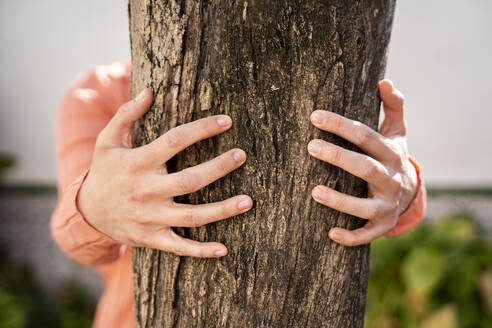 Woman embracing tree trunk in garden - AFVF08269