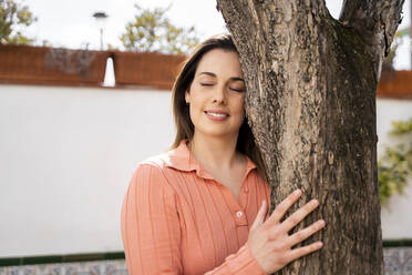 Smiling woman with eyes closed embracing tree trunk in garden - AFVF08272
