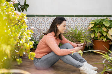 Smiling woman using mobile phone while sitting in garden - AFVF08278