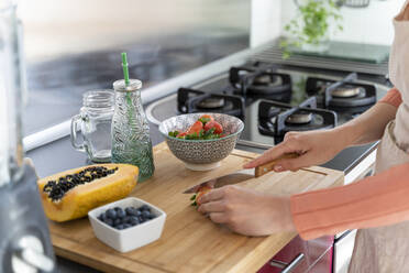 Young woman making healthy fruit smoothie in kitchen. Recipe, videochat, connected, healthy lifestyle, health, fruit, cute, beautiful, stay at home - AFVF08281