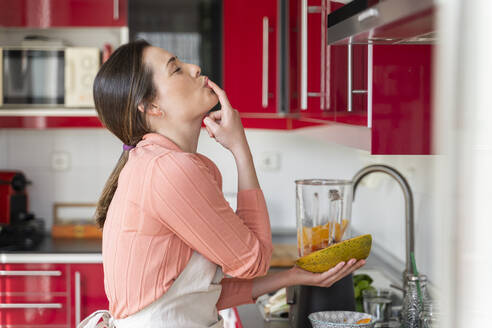 Beautiful woman licking finger while preparing fruit smoothie in kitchen at home - AFVF08290