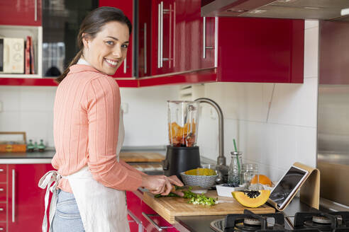 Cheerful woman cutting fresh vegetables in kitchen at home - AFVF08293