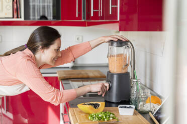 Young woman making healthy fruit smoothie in kitchen. Recipe, videochat, connected, healthy lifestyle, health, fruit, cute, beautiful, stay at home - AFVF08296
