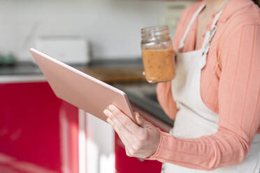 Young woman making healthy fruit smoothie in kitchen. Recipe, videochat, connected, healthy lifestyle, health, fruit, cute, beautiful, stay at home - AFVF08302