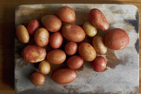 Raw potatoes lying on wooden cutting board - SABF00062