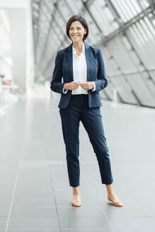 Mature female entrepreneur standing in corridor - JOSEF03614