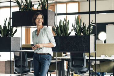 Smiling businesswoman with smart phone looking away while standing in office - JOSEF03620