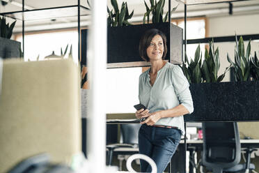 Mature businesswoman with mobile phone looking away while standing in office - JOSEF03623