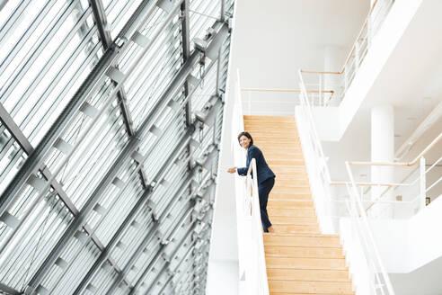 Mature businesswoman standing on steps in corridor - JOSEF03626