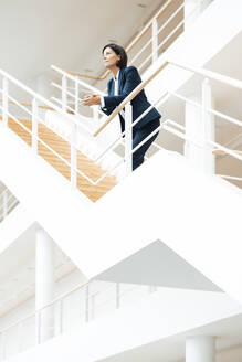 Businesswoman leaning on railing while standing over steps in corridor - JOSEF03632