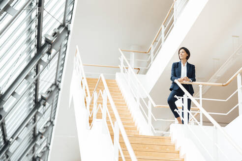 Female professional by railing standing on staircase in corridor - JOSEF03638