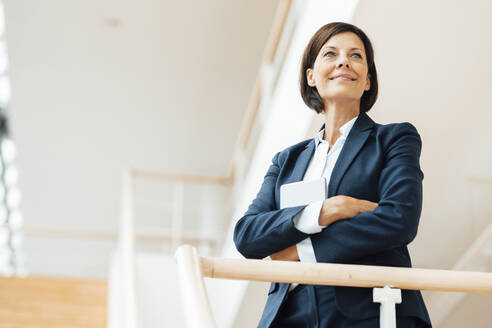 Smiling female entrepreneur with arms crossed standing by railing at office - JOSEF03644