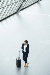 Female entrepreneur with suitcase talking on mobile phone while standing at corridor - JOSEF03647