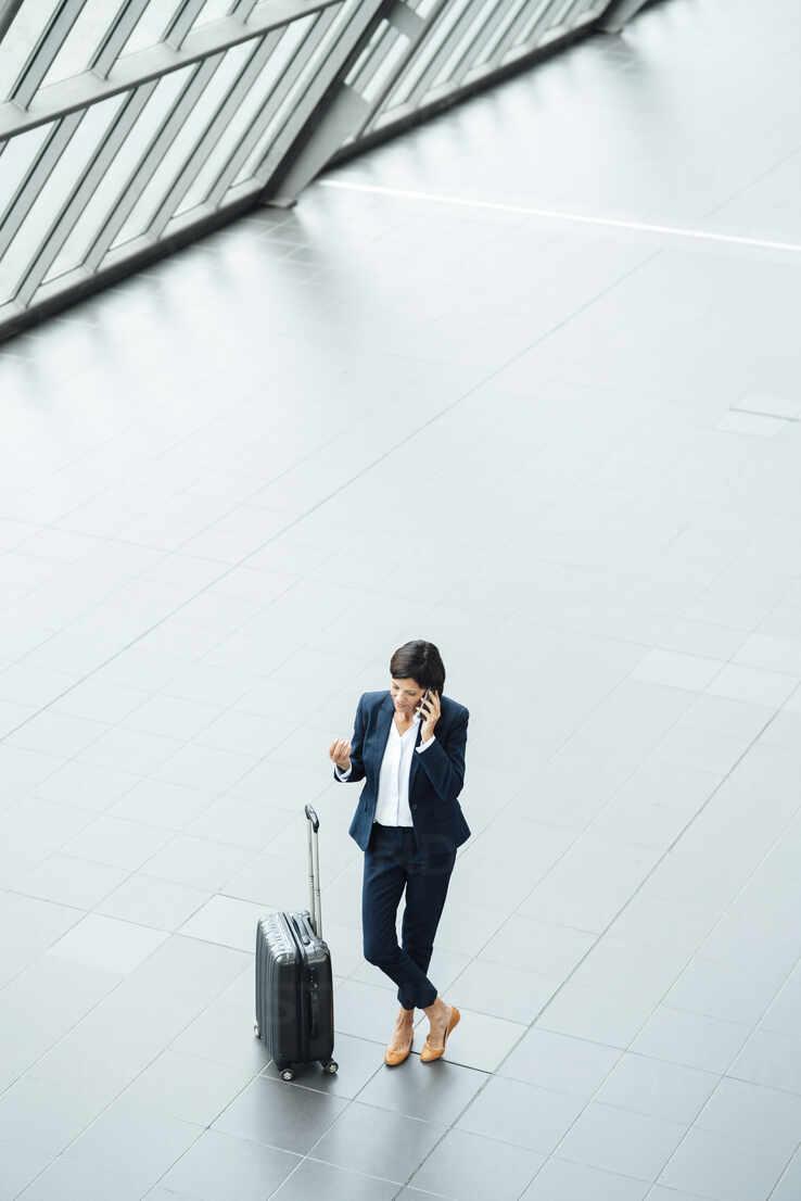 Weibliche Unternehmerin mit Koffer spricht am Handy, während sie im Flur steht - JOSEF03647 - Joseffson/Westend61