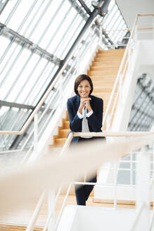Smiling female entrepreneur with hand on chin leaning over railing in corridor - JOSEF03653