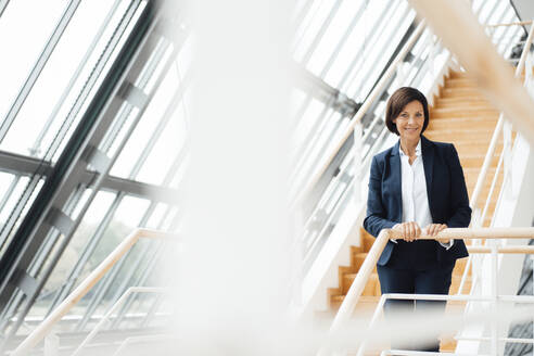 Smiling businesswoman holding railing while standing on steps - JOSEF03656