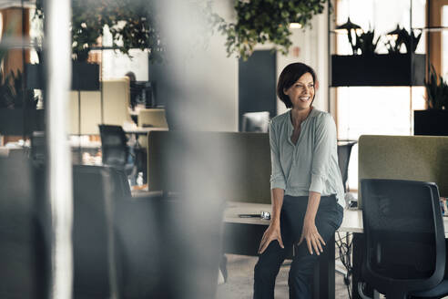 Happy businesswoman looking away while leaning on desk in office - JOSEF03665