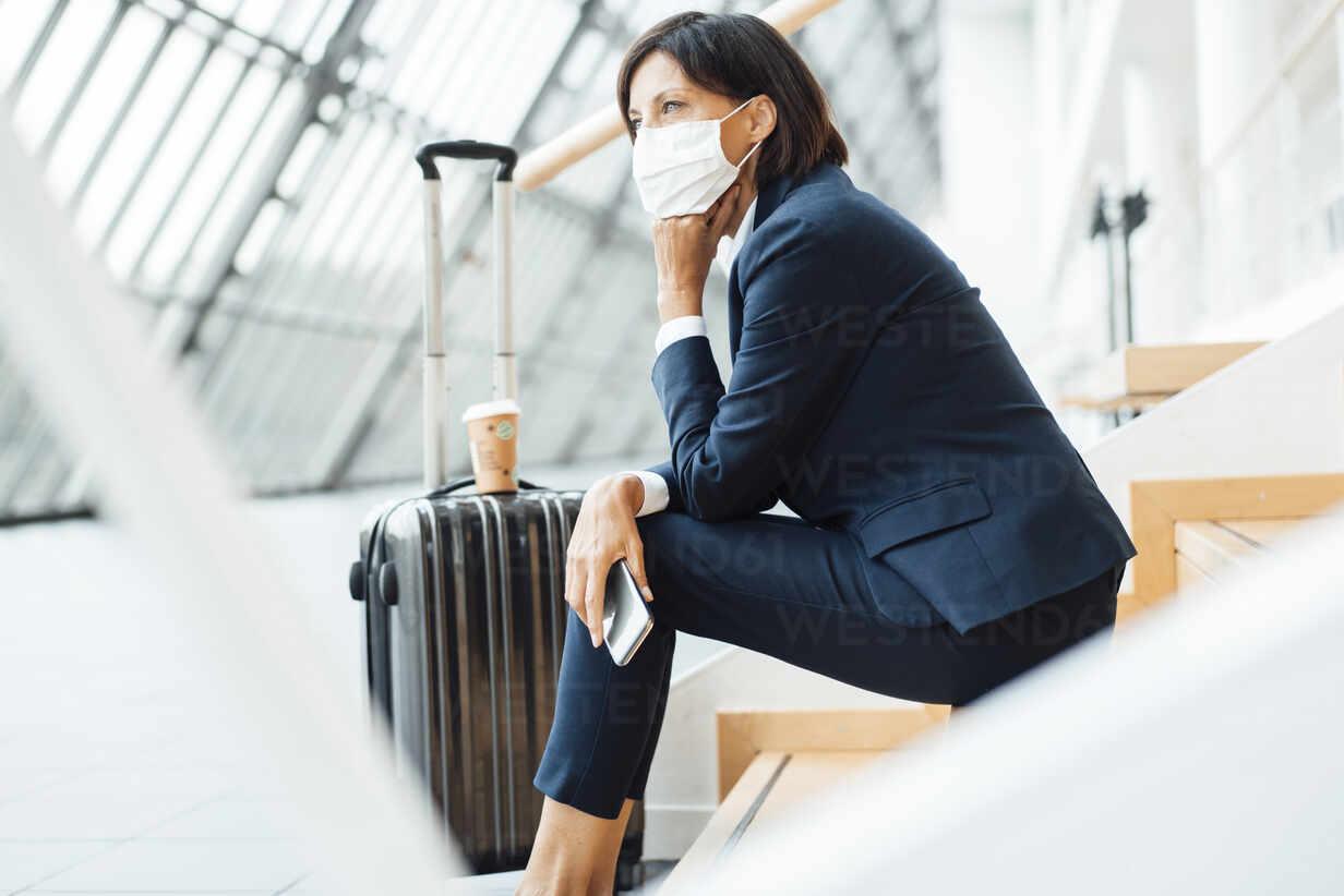 Weibliche Unternehmerin mit Hand am Kinn über Stufen im Korridor sitzend während der Pandemie - JOSEF03671 - Joseffson/Westend61