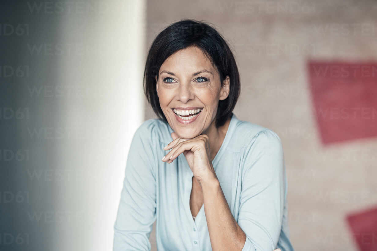 Geschäftsfrau lachend mit Hand am Kinn im Büro gegen die Wand - JOSEF03677 - Joseffson/Westend61