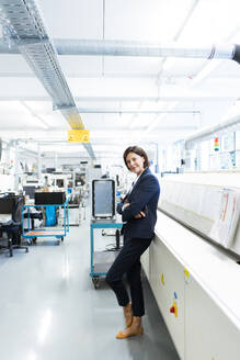 Female entrepreneur with arms crossed in factory - JOSEF03689