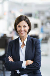 Smiling confident businesswoman with arms crossed in office - JOSEF03698