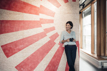 Smiling businesswoman with coffee cup against wall at office - JOSEF03716