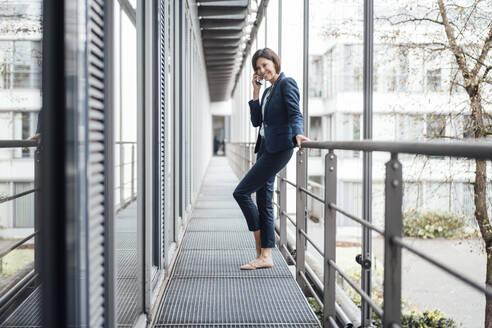 Smiling female entrepreneur talking on smart phone against railing in balcony - JOSEF03725