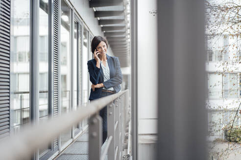 Female professional talking on mobile phone while standing in office balcony - JOSEF03728