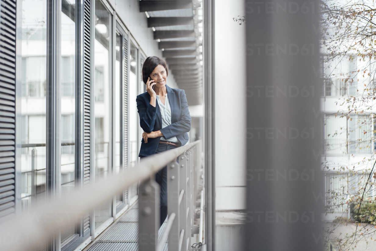 Weibliche professionelle Gespräch am Handy, während in Büro Balkon stehen - JOSEF03728 - Joseffson/Westend61