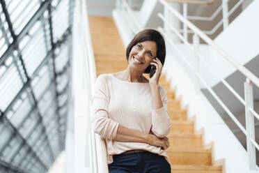 Smiling female entrepreneur talking on smart phone against steps - JOSEF03734