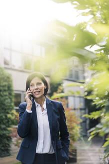 Female professional talking on smart phone at office park - JOSEF03743