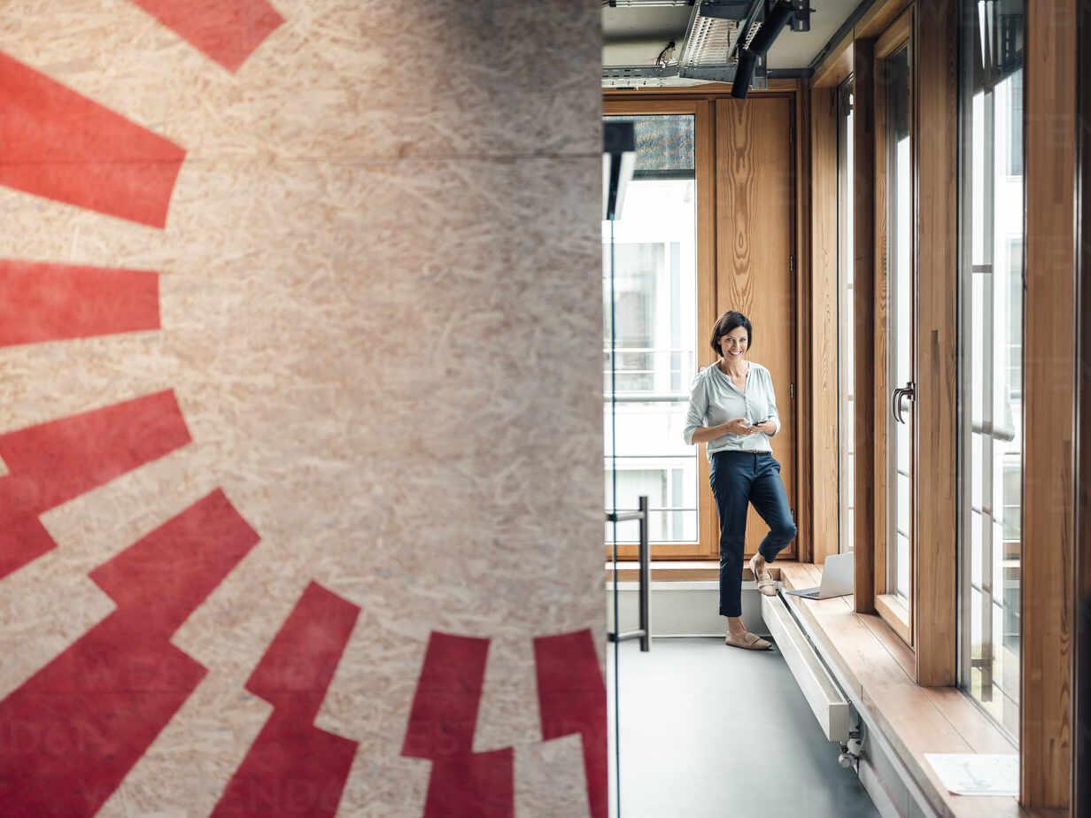 Female professional standing by window at office - JOSEF03746 - Joseffson/Westend61