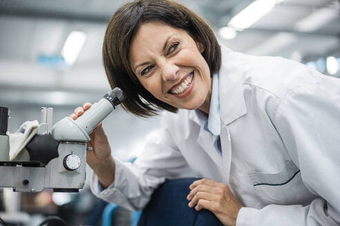 Smiling female scientist holding microscope at laboratory - JOSEF03755