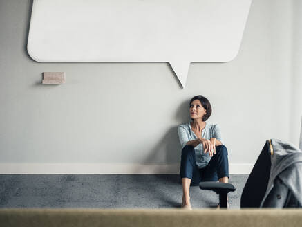 Thoughtful businesswoman looking up while sitting on floor at office - JOSEF03761
