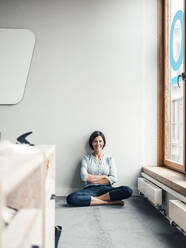 Businesswoman with arms crossed sitting on floor at office against wall - JOSEF03764