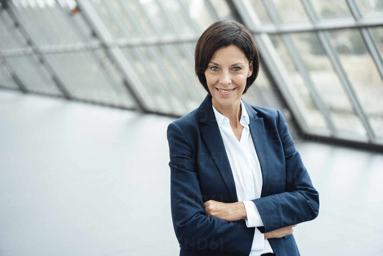 Mature businesswoman with arms crossed at office in corridor - JOSEF03767 - Joseffson/Westend61