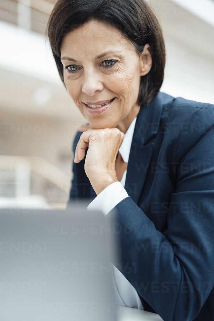 Lächelnder Geschäftsmann mit Hand am Kinn mit Laptop im Büro - JOSEF03776 - Joseffson/Westend61