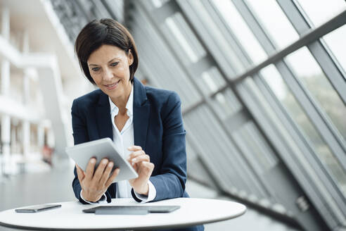 Smiling businesswoman using digital tablet at desk in corridor - JOSEF03779