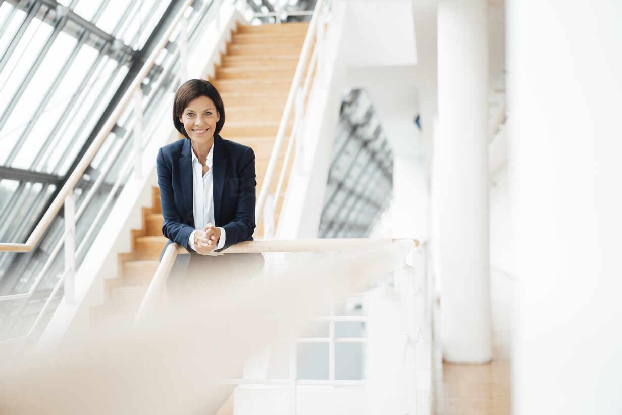 Smiling female professional leaning on railing at corridor - JOSEF03788 - Joseffson/Westend61