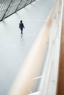 Businesswoman walking in corridor at office - JOSEF03791