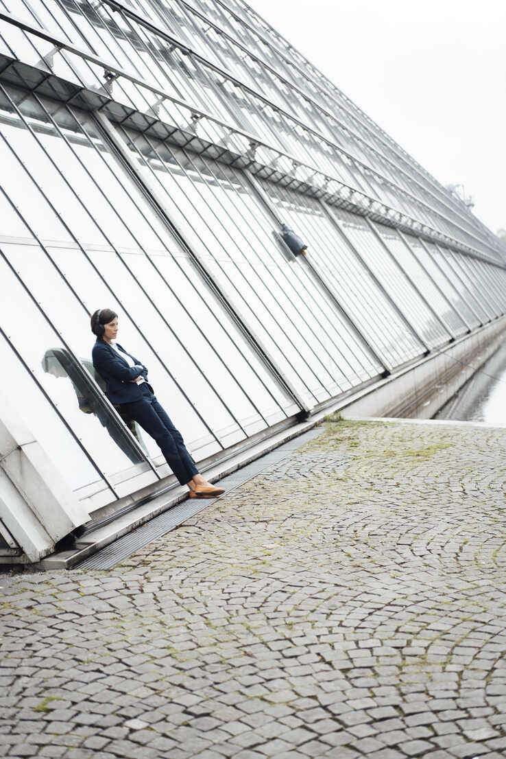 Female professional leaning against wall at lakeshore - JOSEF03800 - Joseffson/Westend61