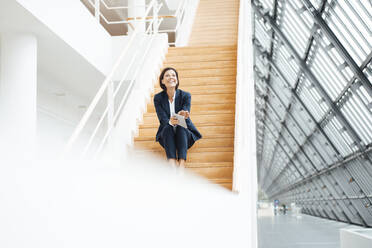 Businesswoman with digital tablet laughing while sitting on steps in corridor - JOSEF03809