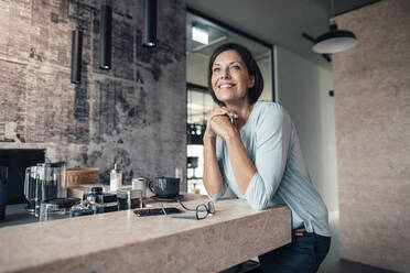 Female entrepreneur looking away while leaning on table in office - JOSEF03815