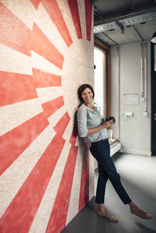 Smiling businesswoman with coffee cup leaning on wall at office - JOSEF03818